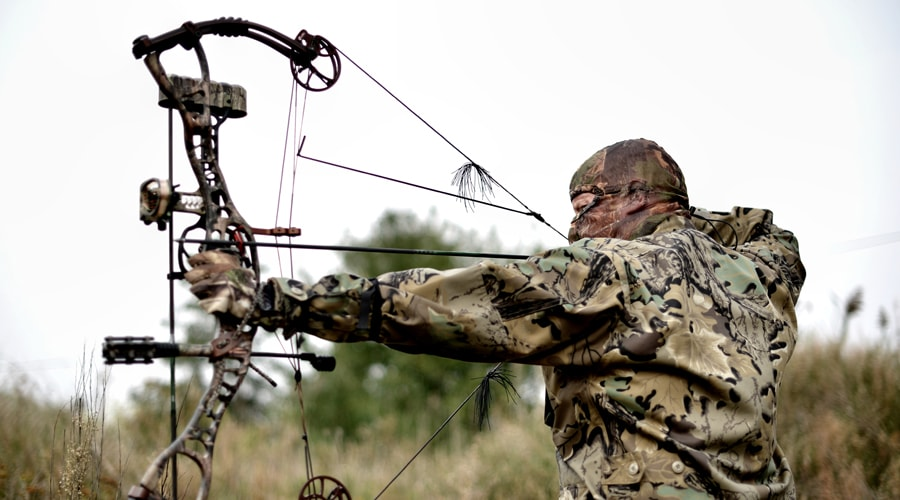 man with compound bow demonstrates how to get into bow hunting
