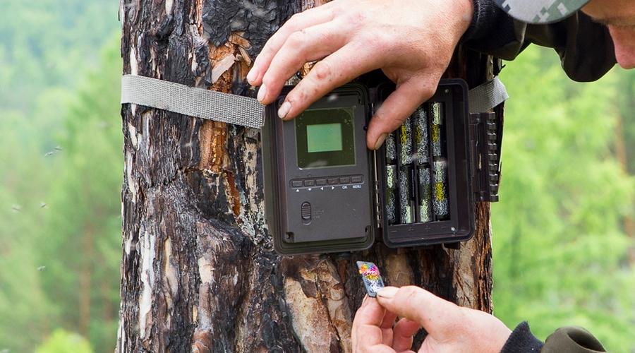 a man demonstates how to program a trail camera